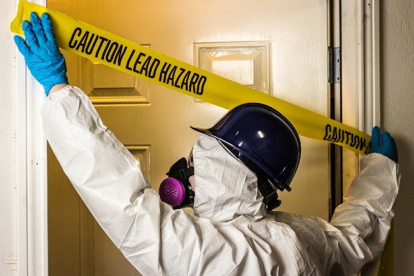HAZMAT worker places caution tape over home with dangerous lead or asbestos